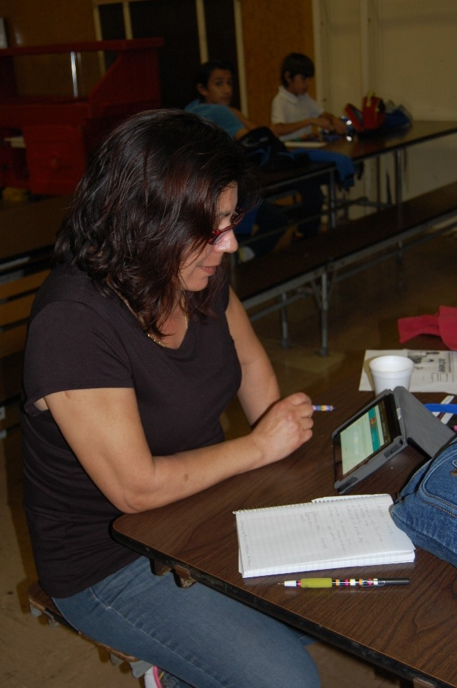 Woman sitting at a desk with a notebook and electronic device